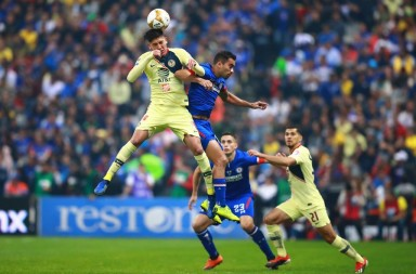 MEXICO CITY, MEXICO - DECEMBER 16: Edson Alvarez #4 of America heads the ball against Adrian Aldrete #16 of Cruz Azul during the final second leg match between Cruz Azul and America as part of the Torneo Apertura 2018 Liga MX at Azteca Stadium on December 16, 2018 in Mexico City, Mexico. (Photo by Hector Vivas/Getty Images)