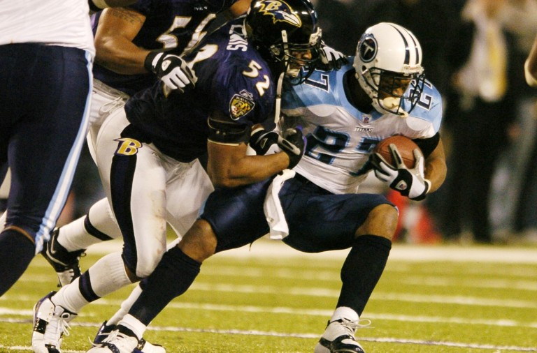 Tennessee Titans running back Eddie George (27) is tackled by Baltimore Ravens linebacker Ray Lewis (52) and Edgerton Hartwell (56) during the fourth quarter of the Titans' 20-17 win in a playoff game, Saturday, Jan. 3, 2004, in Baltimore. (AP Photo/Nick Wass)